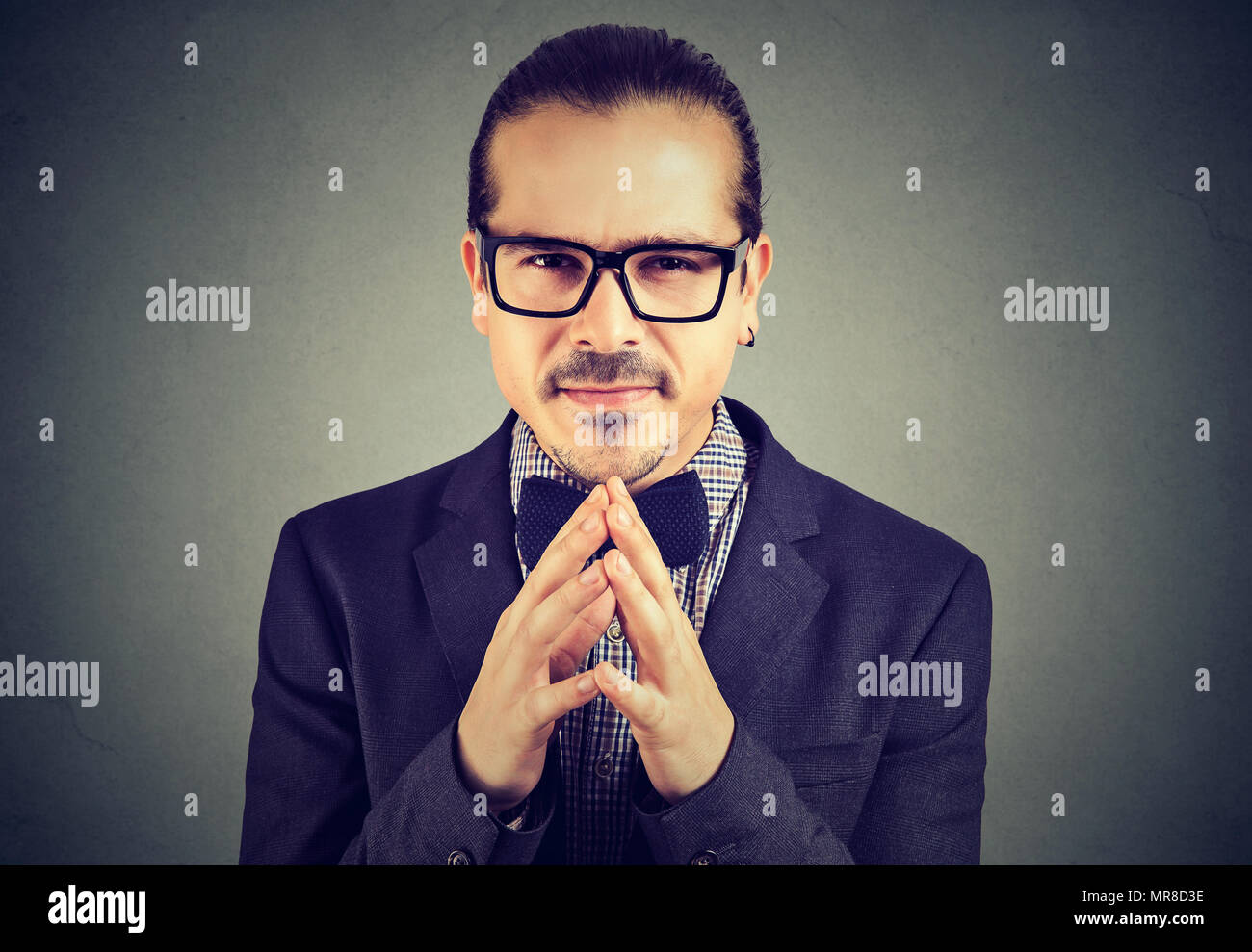 Sly business man in glasses looking at camera plotting a revenge - Stock Image