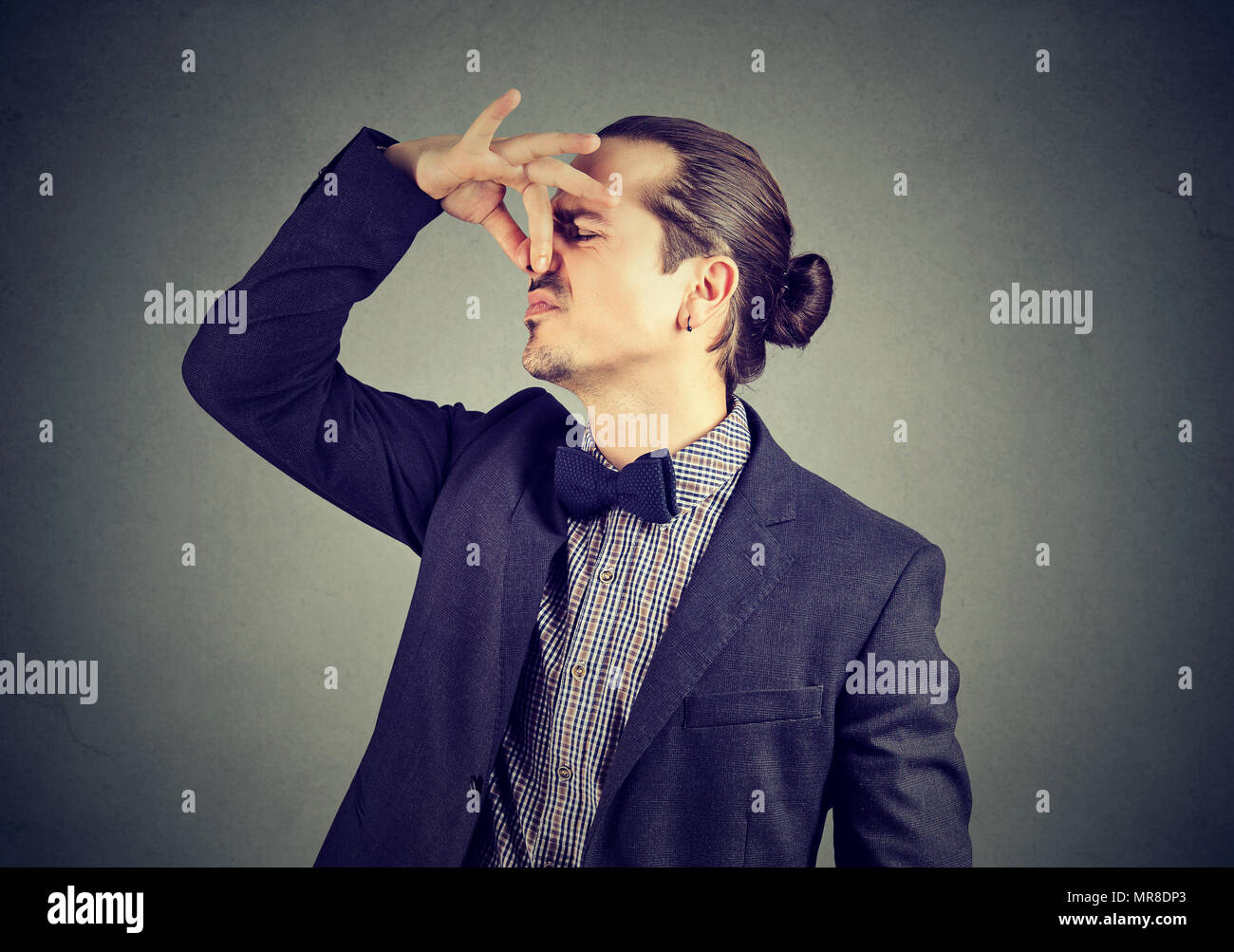 Disgusted man pinches nose with fingers looks with disgust something stinks bad smell isolated on wall background. Human face expression reaction - Stock Image