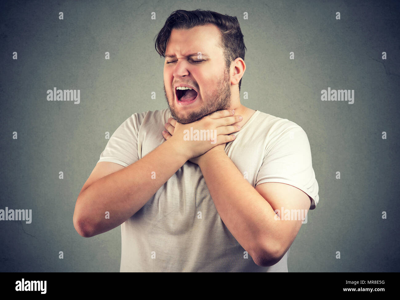 Chunky casual man frowning and suffocating having allergy and holding hands on neck with eyes closed. - Stock Image