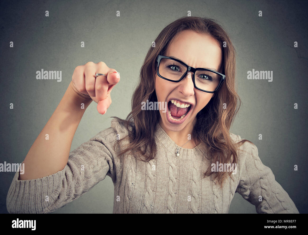 Young girl in glasses pointing at camera and shouting in accusation looking angry on gray background. - Stock Image