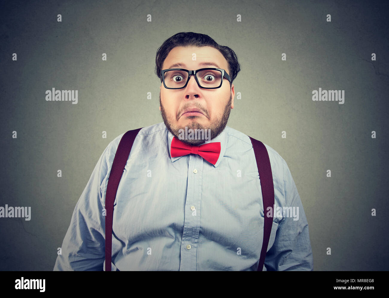 Funny obese man in bow tie and glasses looking awkward and perplexed on gray background. - Stock Image