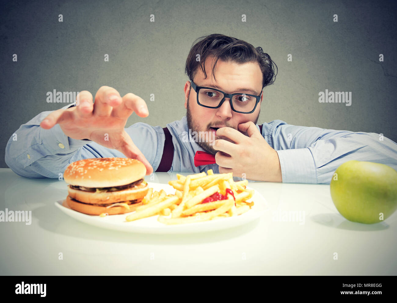 Young obese man in glasses having cravings for cheeseburger with fries instead of healthy green apple. - Stock Image