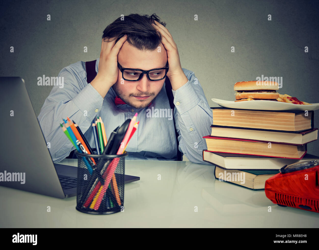 Overworked stressed chubby man sitting at desk and craving a burger - Stock Image