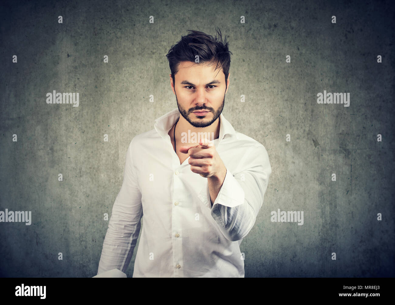 Young blaming man in white shirt pointing with finger at camera indicating person and looking serious on gray background. - Stock Image