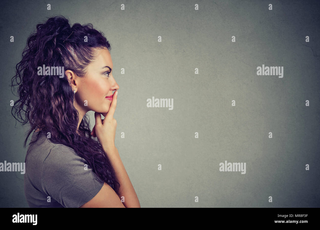 Side view of pretty brunette touching lips in contemplation and looking away thinking of idea on gray background. - Stock Image