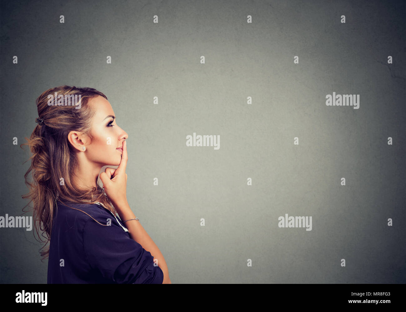 Side view of a pretty brunette woman in contemplation looking away thinking of idea on gray background. - Stock Image