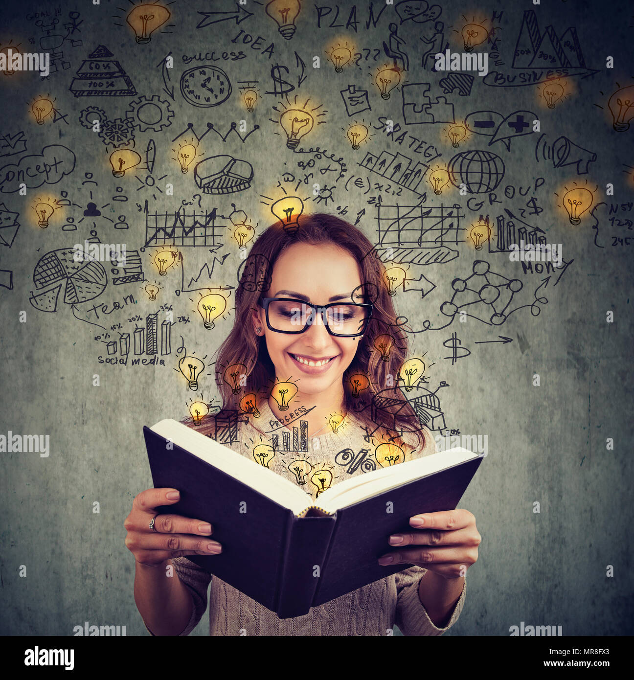 Young girl in glasses reading big book and having plenty of successful ideas looking happy on gray background. - Stock Image