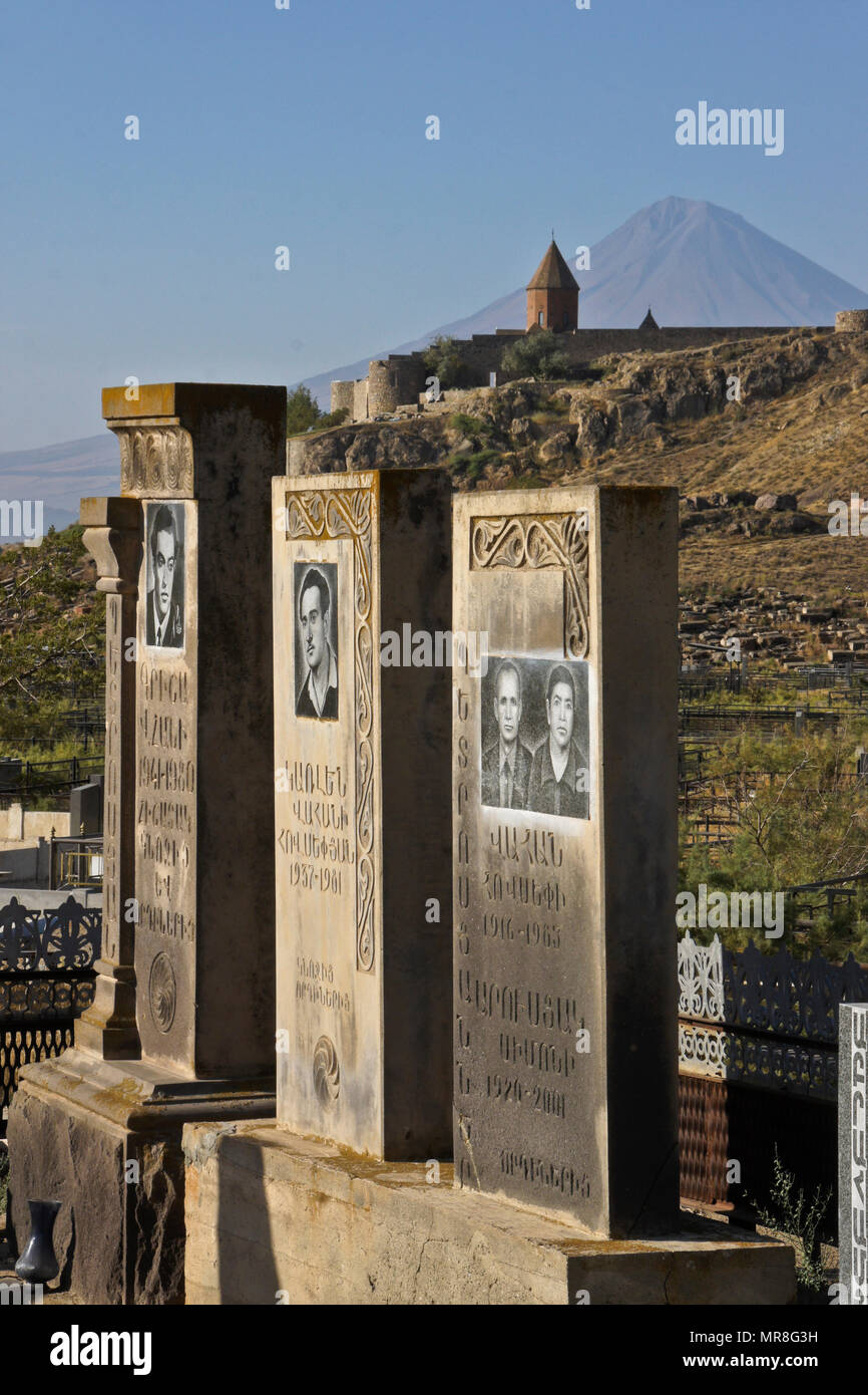 The peak of Little Mount Ararat rises behind a cemetery below Khor Virap Monastery in Armenia. Many tombstones include photographs of the deceased. - Stock Image