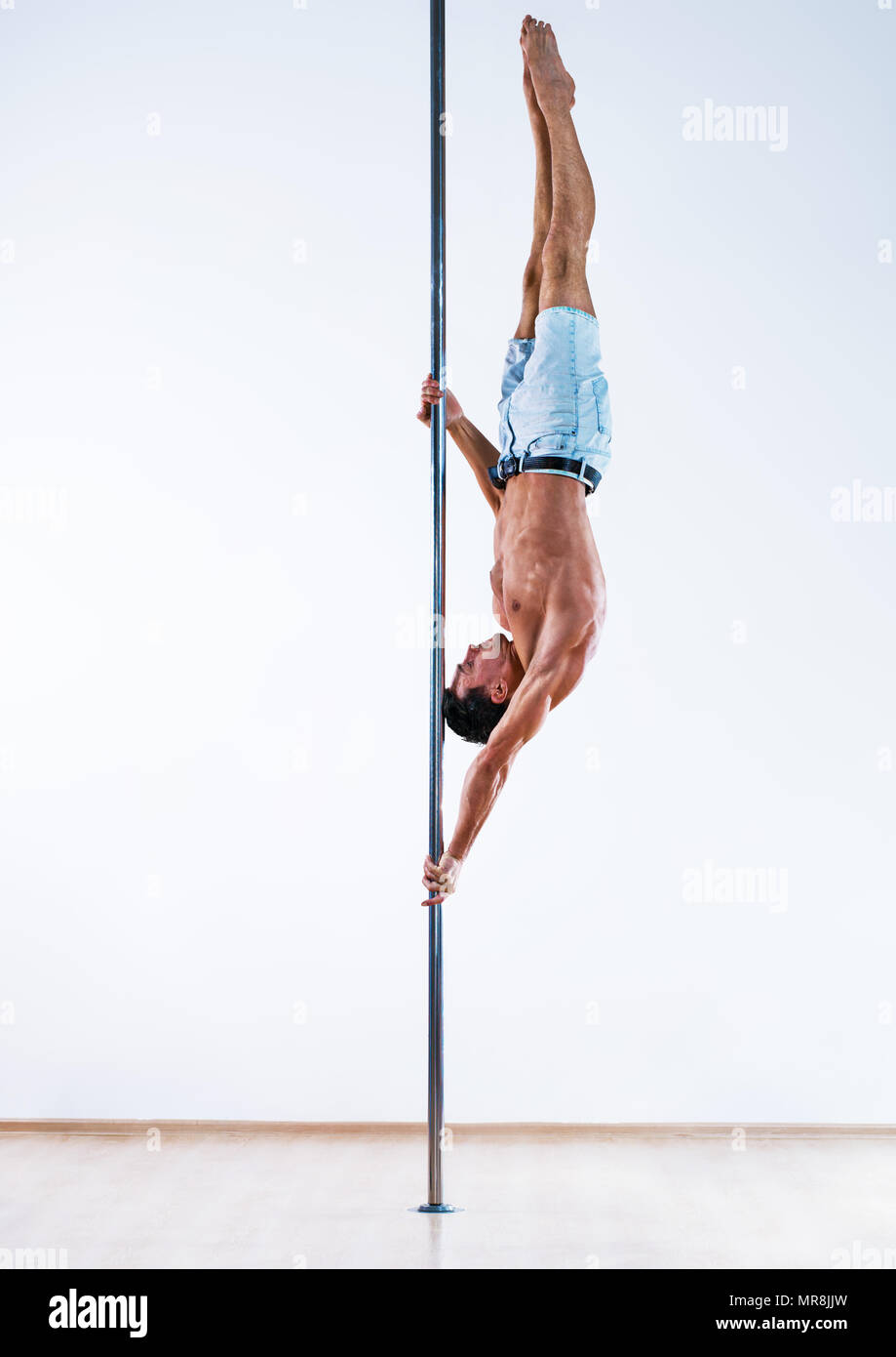 Young pole dancing man on white wall background - Stock Image
