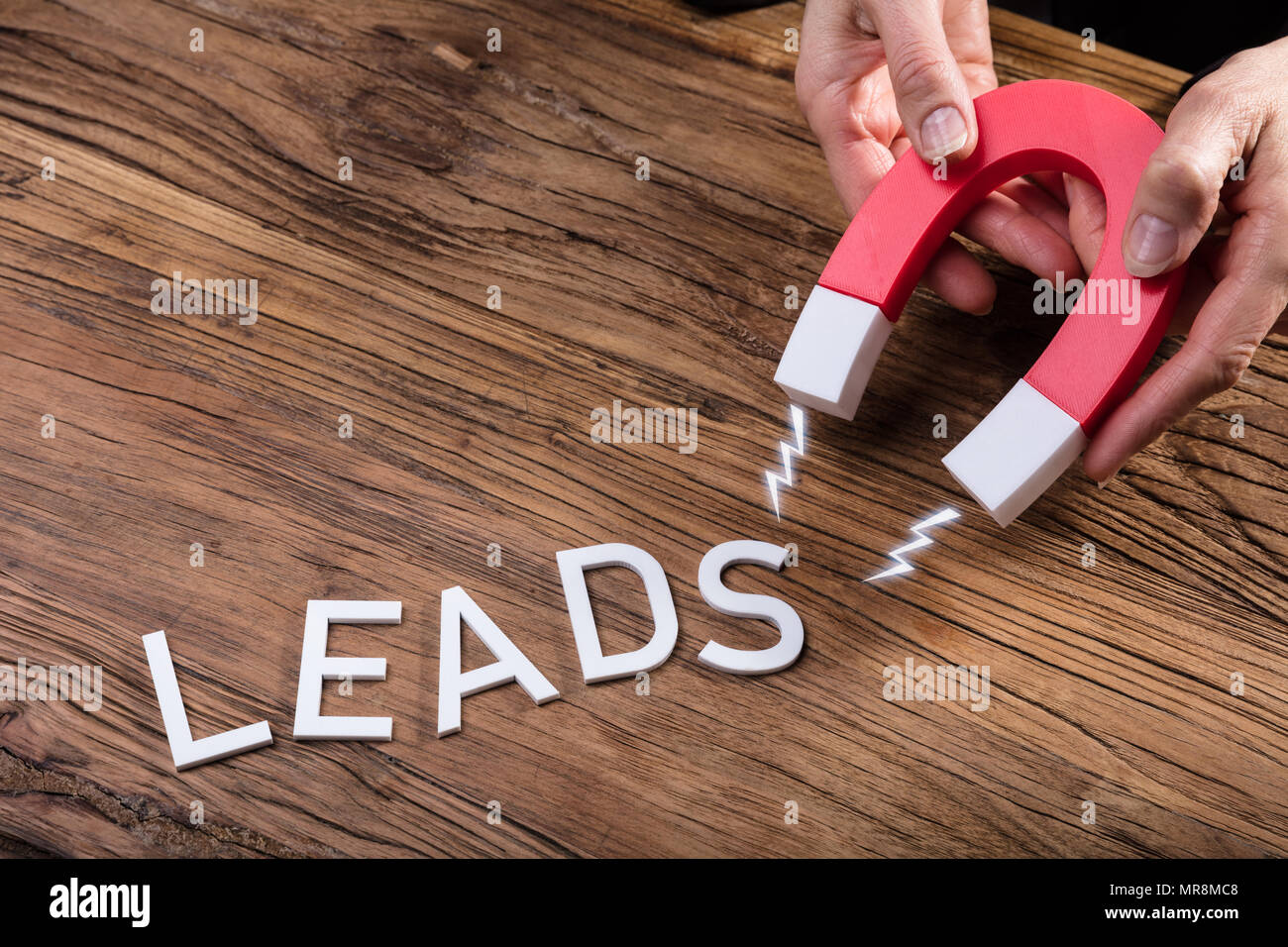 Businessperson Attracting White Lead Text With Horseshoe Magnet Over Wooden Desk - Stock Image