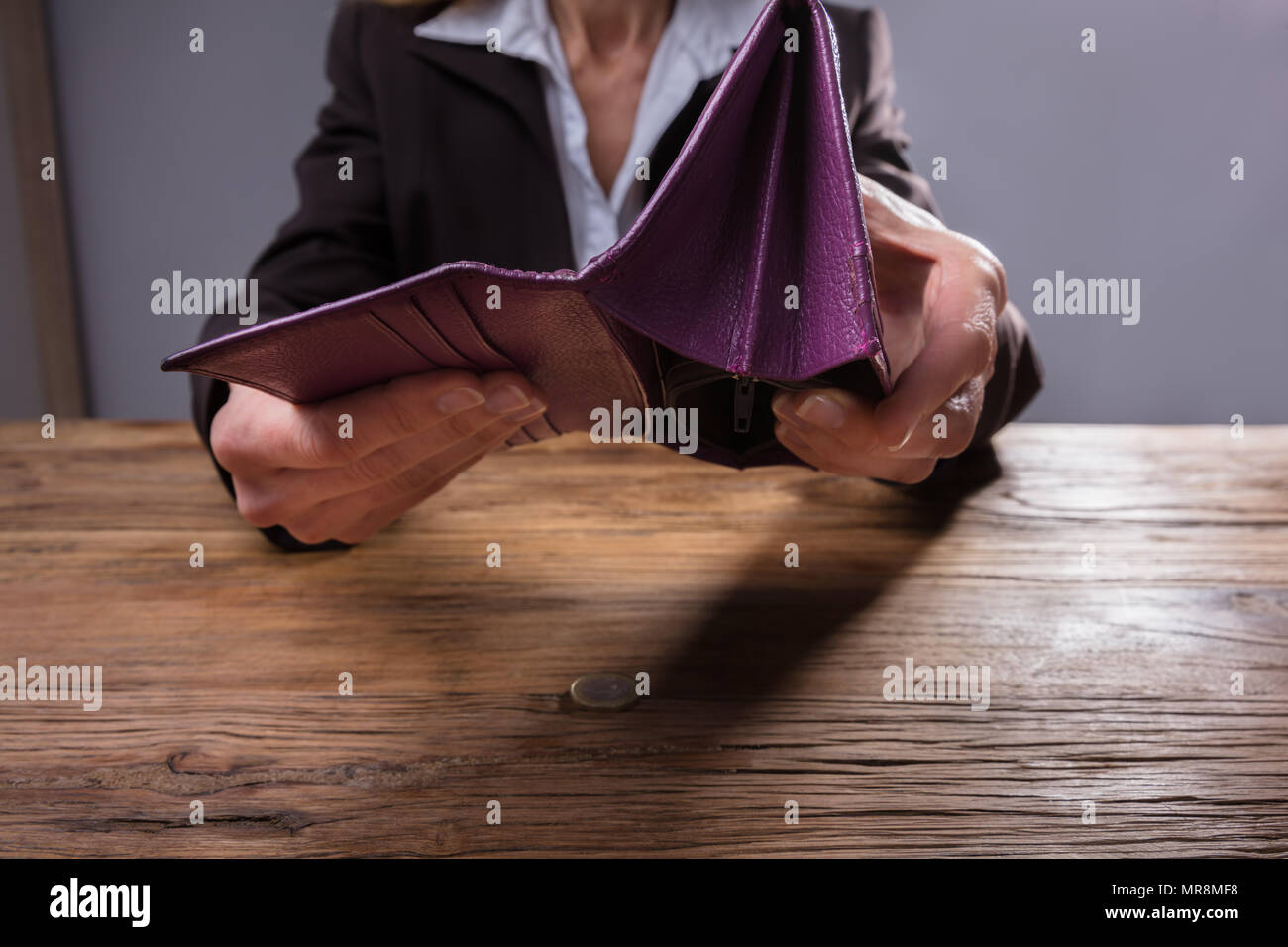 Close-up Of A Businessperson's Hand Holding Empty Purse Over Wooden Desk Stock Photo