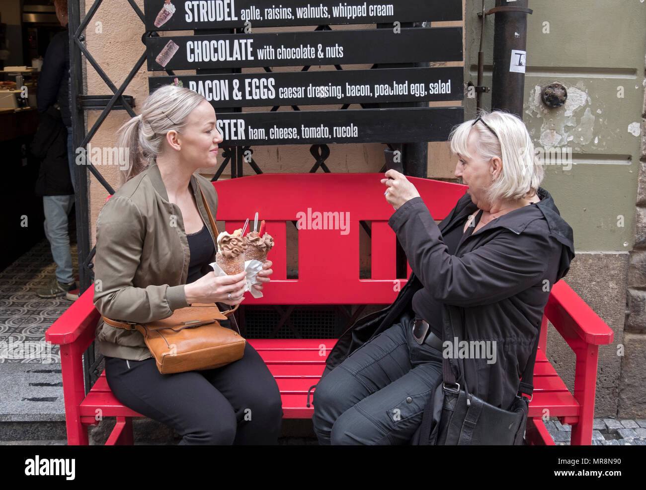 A woman takes a cell phone photograph of a younger lady with the Trdelnik ice creams they are about to eat. In Old Town Prague, Czech Republic. - Stock Image
