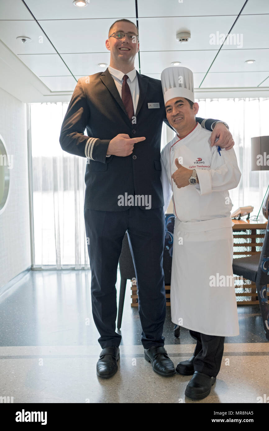 On a Viking Cruise ship the 6 foot 7 Hotel Manager poses with the 5 foot 2 Head chef. On a Danube River cruise. - Stock Image
