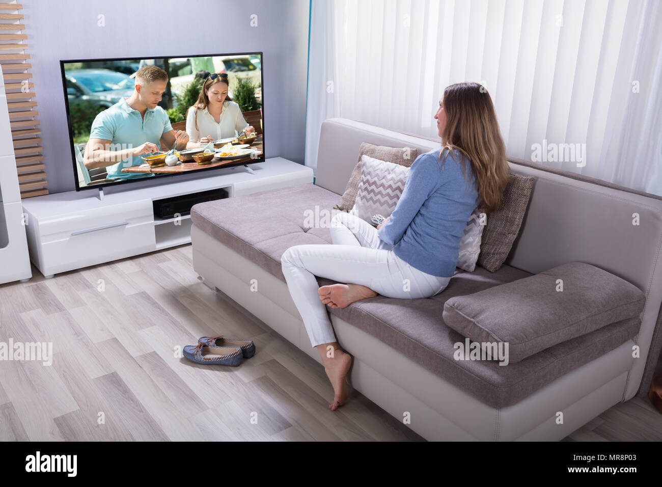 Mature Woman Sitting On Sofa Watching Television At Home - Stock Image
