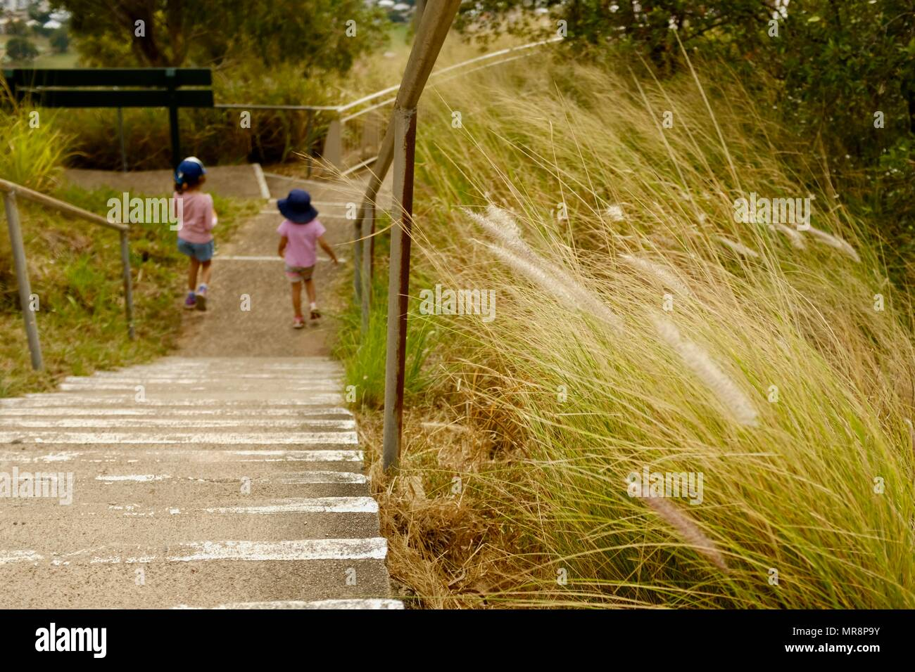 Two children at the bottom of a flight of stairs surrounded by long grass, Castle Hill QLD 4810, Australia - Stock Image