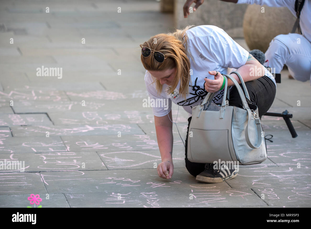 A woman writes messages in chalk on the pavement in St Ann's Square