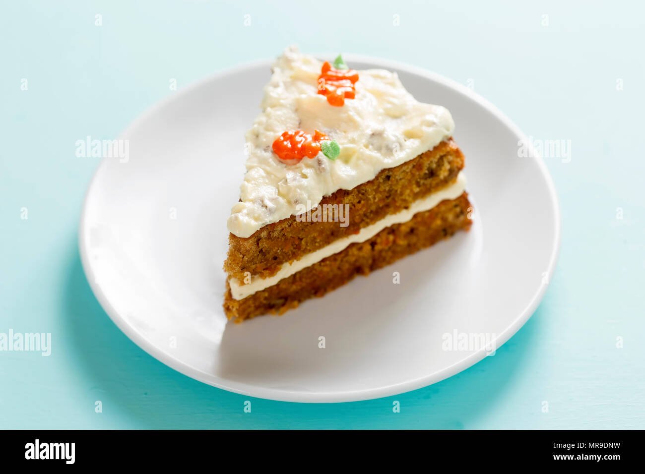 Slice of carrot cake with frosting and carrot decoration. - Stock Image