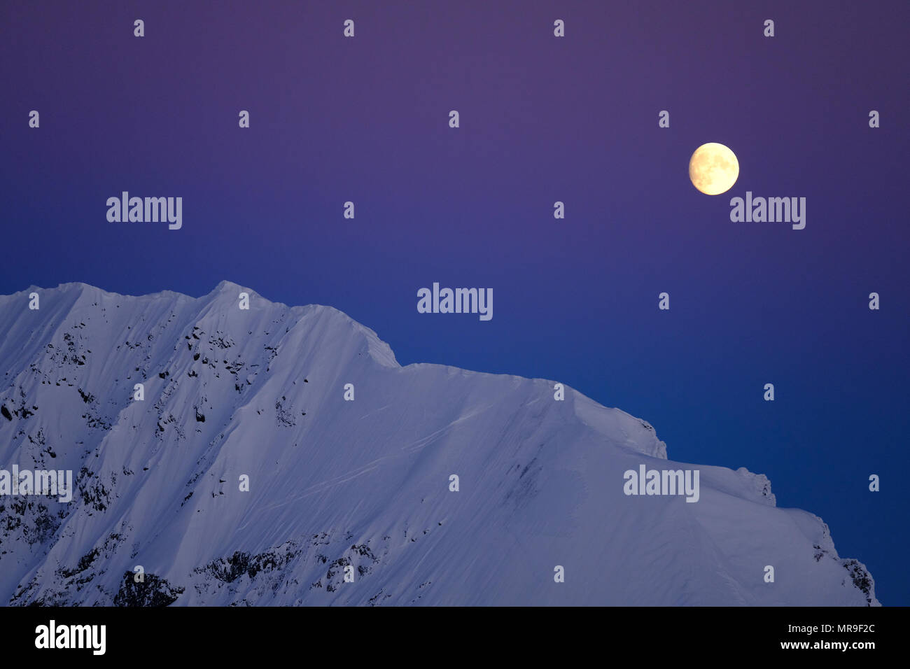 Moon rising over Peak 7460, Chugach Mountains, Alaska - Stock Image