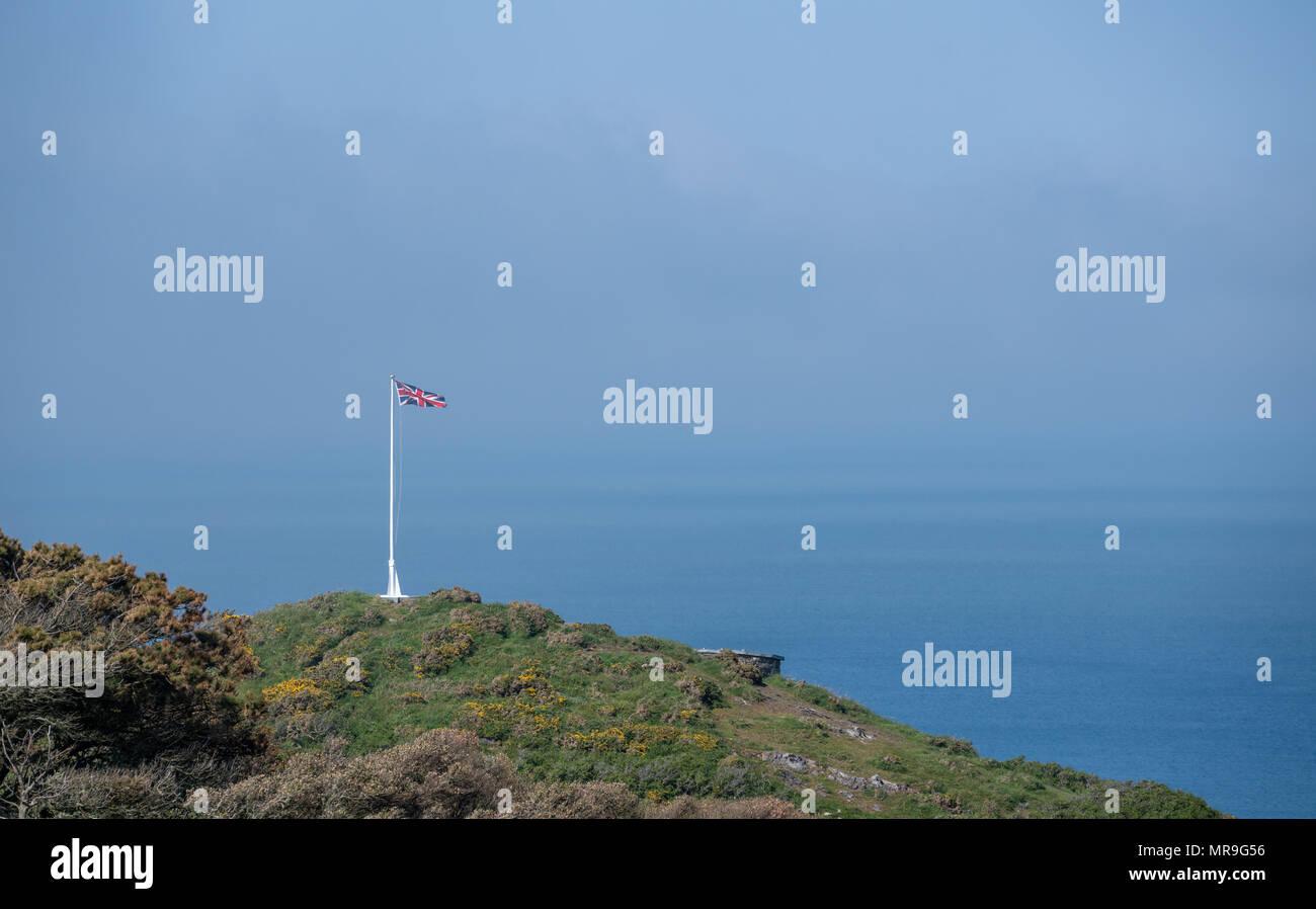 Union flag and flagpole on headland above the sea - Stock Image