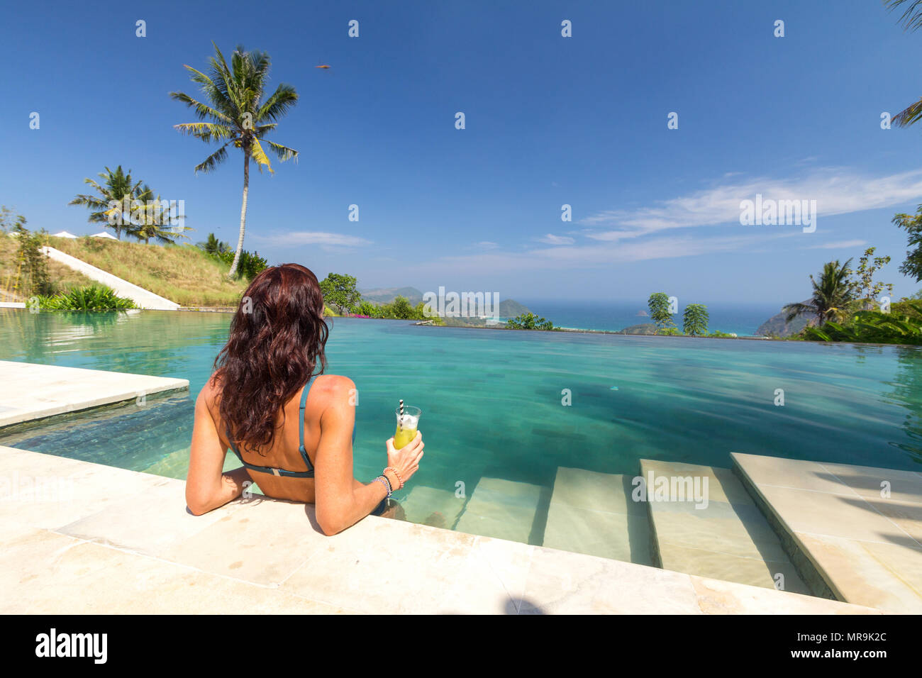 Girl at infinity pool - Stock Image
