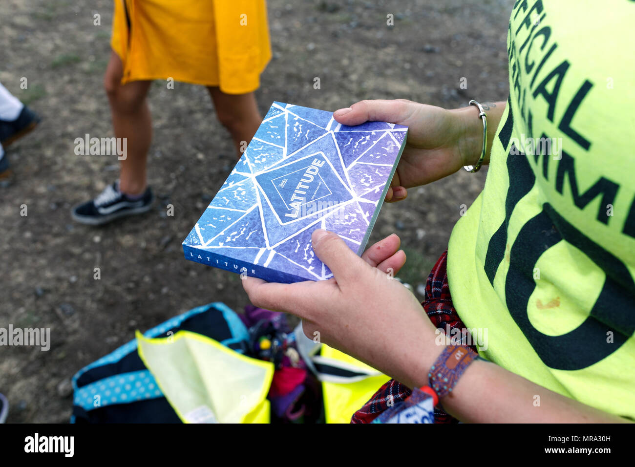 A programme seller holding a programme at Latitude Festival 2017. - Stock Image