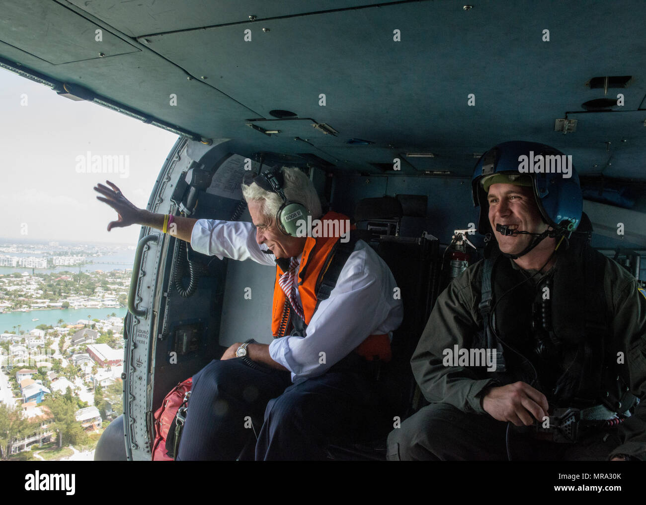Congressman Charlie Crist, U.S. Representative for Florida's 13th District, waves to beachgoers Tuesday, May 30, 2017, alongside Petty Officer 3rd Class Justin Kuchar, crew member at Air Station Clearwater, during an aerial assessment of erosion along Pinellas County, Florida's coast.  U.S. Coast Guard by Petty Officer 1st Class Michael De Nyse - Stock Image