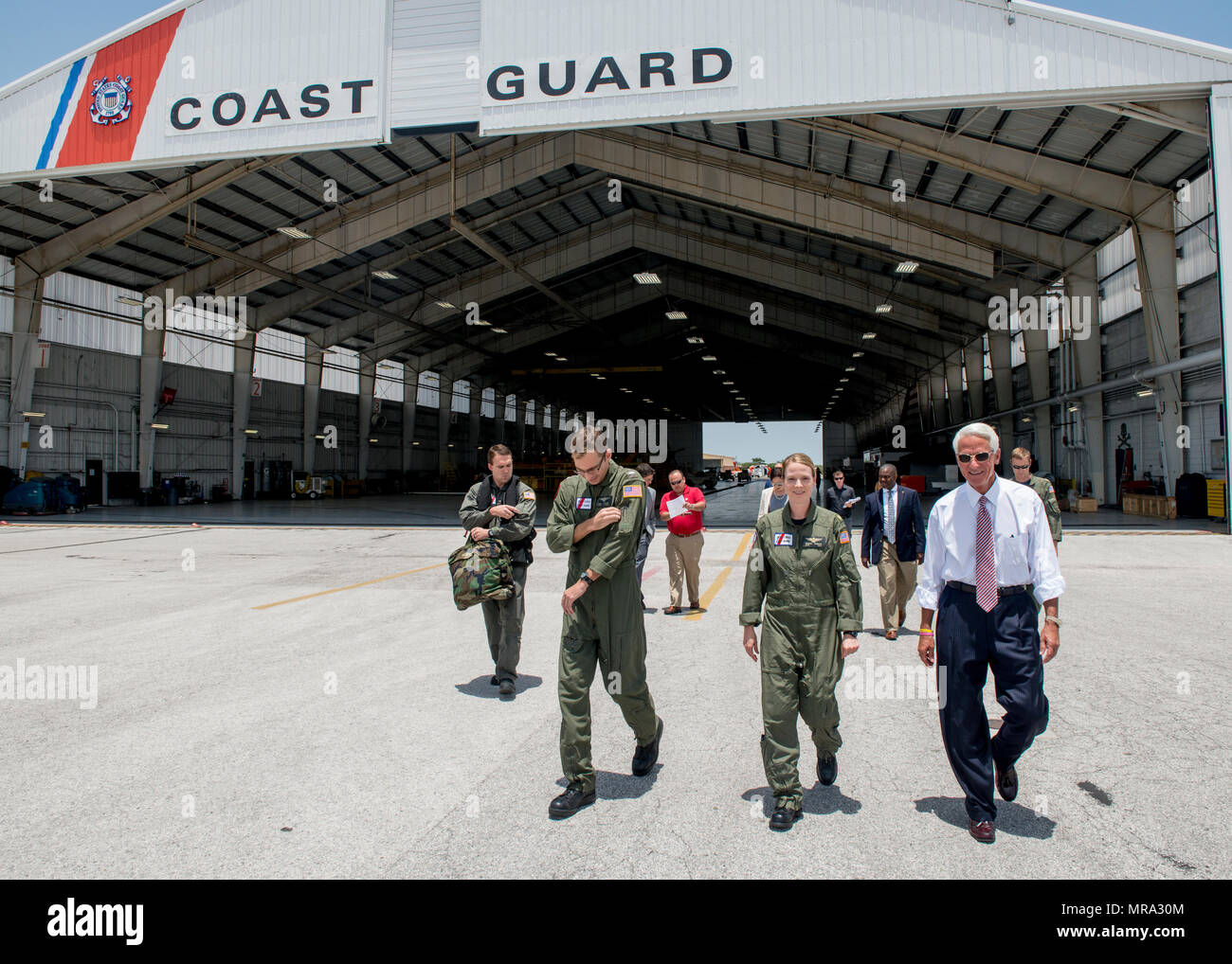 Congressman Charlie Crist, U.S. Representative for Florida's 13th District, right, speaks with Air Station Clearwater crew members Tuesday, May 30, 2017, prior to an aerial assessment of beach erosion along Pinellas County, Florida's coast. Coast Guard Air Station Clearwater MH-60 Jayhawk helicopter crew members provided the overflight for the congressman and Army Corps of Engineers personnel. U.S. Coast Guard by Petty Officer 1st Class Michael De Nyse - Stock Image