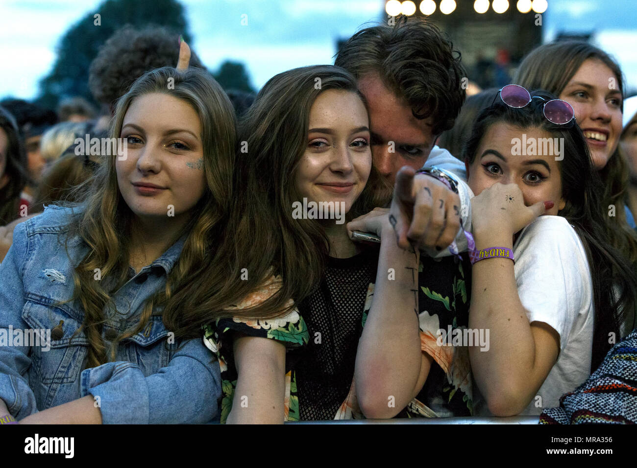 Teenage music fans posing for a photo at a music festival while waiting for a performance by The 1975. - Stock Image