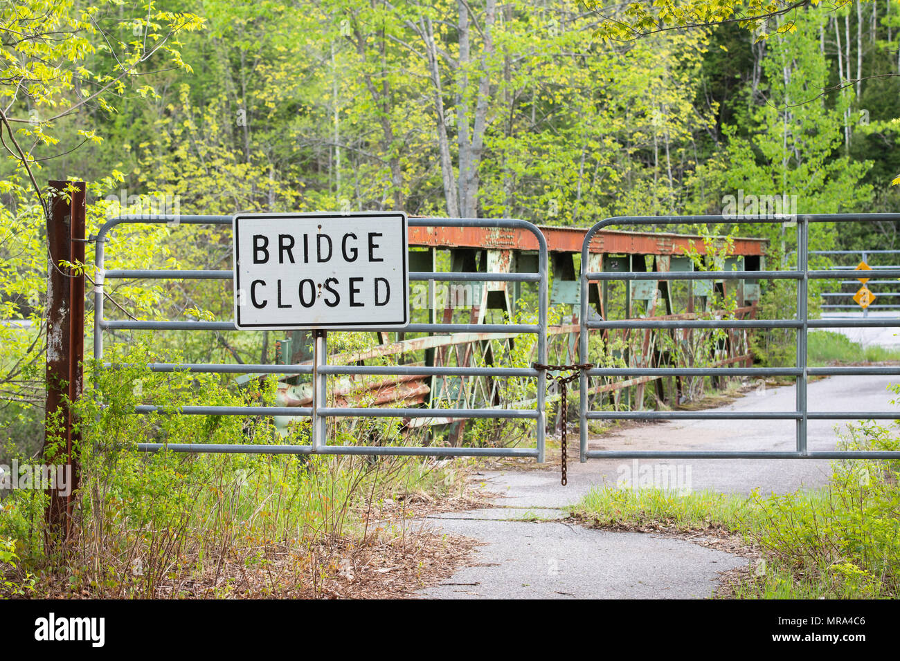 A gate with a bridge closed sign on an unused neglected bridge over the Sacandaga River in the Adirondack, NY wilderness - Stock Image
