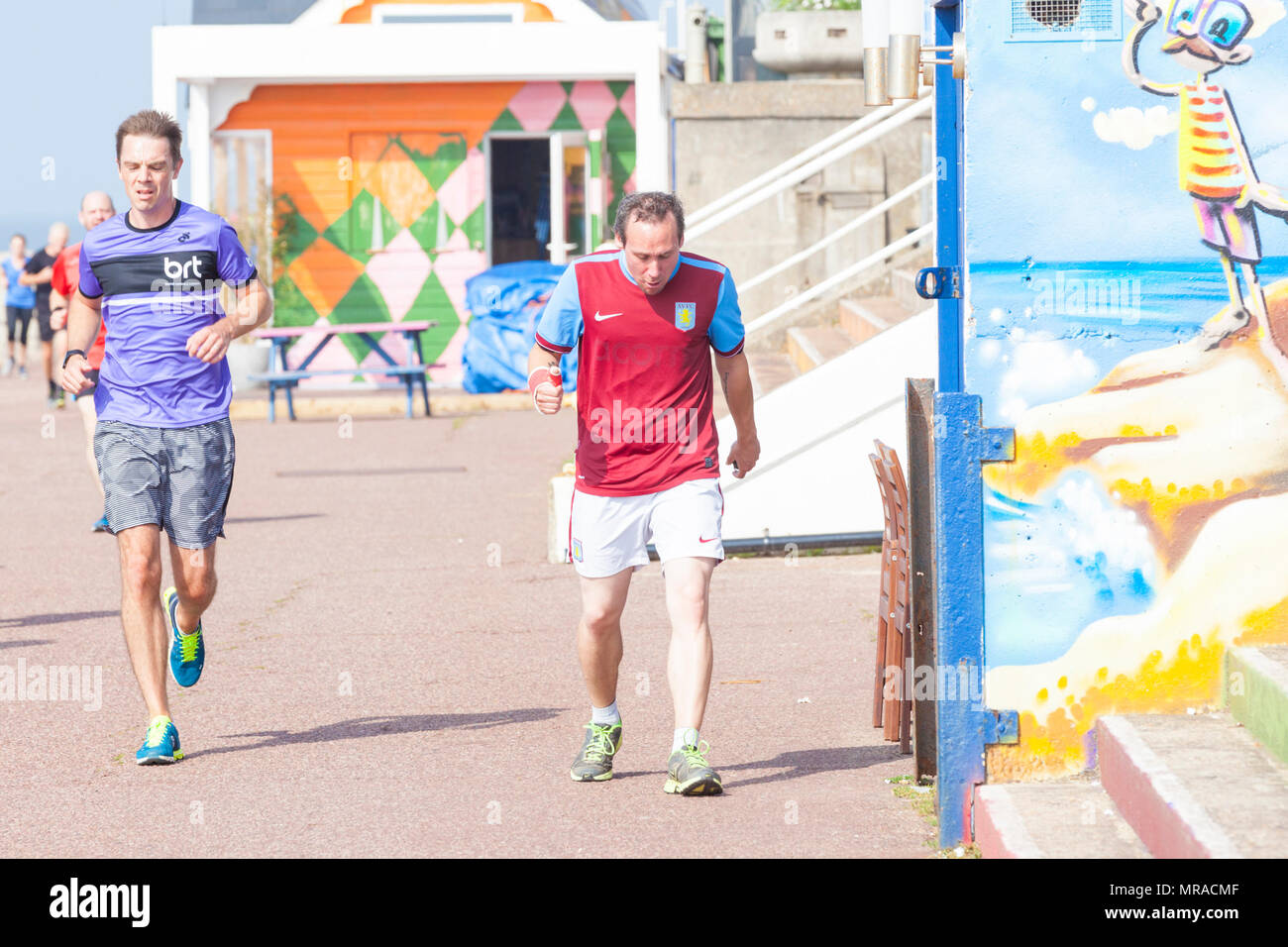 A male jogger wearing an aston villa shirt running along the hastings seafront participating in park run, hastings, east sussex, uk - Stock Image