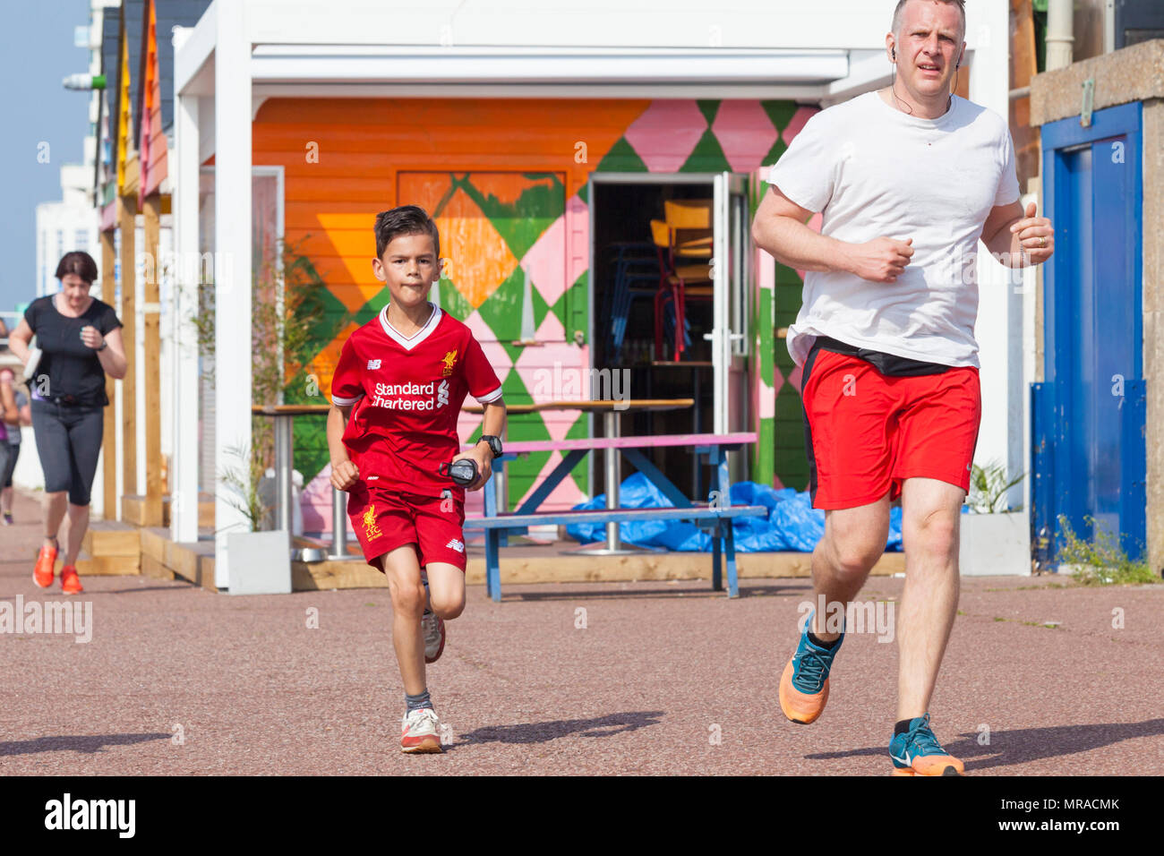 A young jogger wearing a liverpool shirt running along the hastings seafront participating in park run, hastings, east sussex, uk - Stock Image