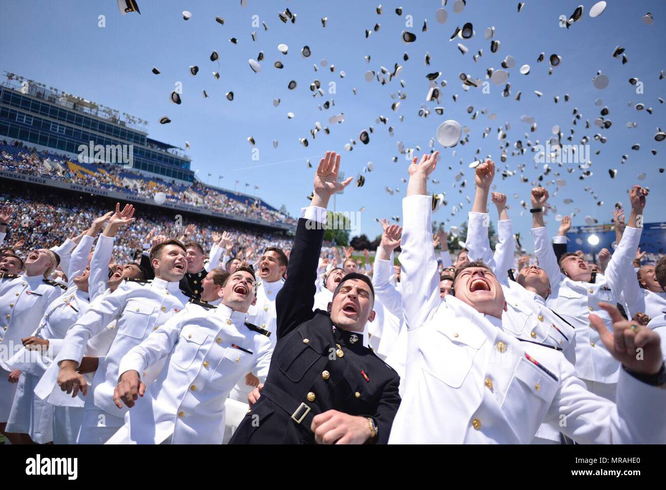 U.S. Naval Academy graduates toss their hats into the air during the annual tradition marking their commissioning and graduation May 25, 2018 in Annapolis, Maryland. The Class of 2018 graduated 1,042 midshipmen and was addressed by President Donald Trump during the ceremony. Stock Photo