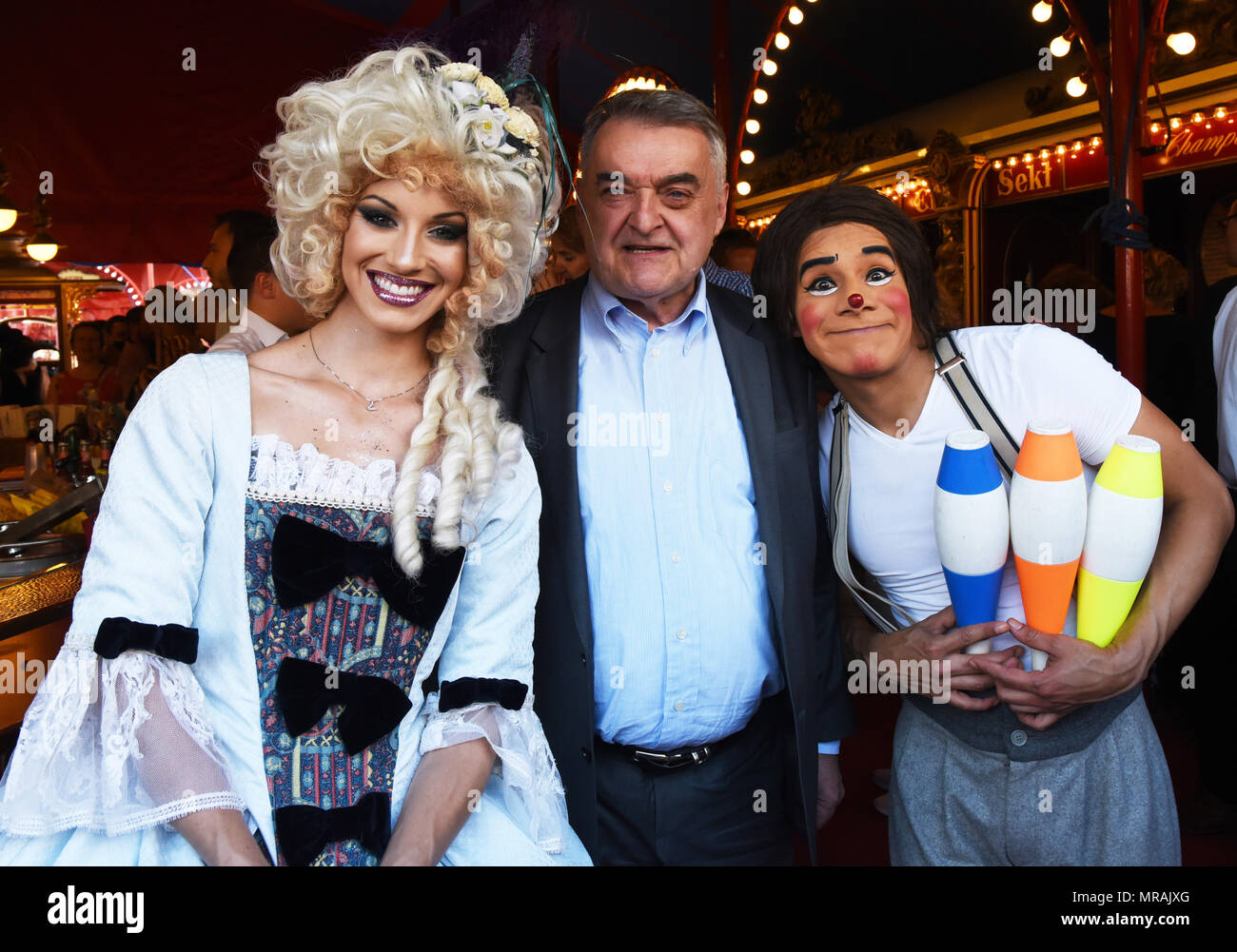25 May 2018, Germany, Duesseldorf: North Rhine-Westphalia's Interior Minister Herbert Reul (C) is greeted by a receptionist and Chisterrin the clown in the evening of the Circus Roncalli's premiere at the Rheinpark, which is featuring the programme 'Storyteller: Yesterday-Today-Tomorrow'. Clowns, magicians and performers will be able to enthrall circus lovers from 25 May until 24 July 2018. However, animals such as horses, elephants and fish will only participate as holograms. Photo: Horst Ossinger//dpa - Stock Image