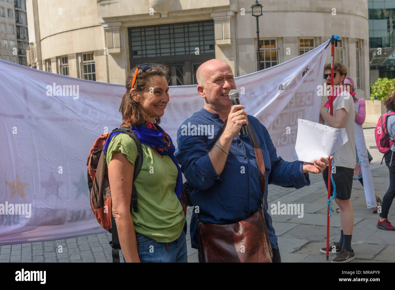 London, UK. 26th May 2018. Mark Campbell, tco-chair of the Kurdistan Solidarity Campaign introduces the aunt of Anna Campbell, the British volunteer killed in Afrin to Kurds and supporters at the rally outside the BBC before marching to Downing St and Parliament Square to call for an end to the Turkish occupation of Afrin. Speakers included the aunt of British volunteer Anna Campbell, killed defending Afrin. Credit: Peter Marshall/Alamy Live News - Stock Image