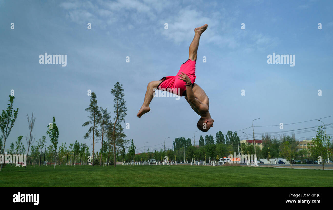 Tricking on lawn in park. Man does back flip and kick. Martial arts and parkour. Street workout. - Stock Image
