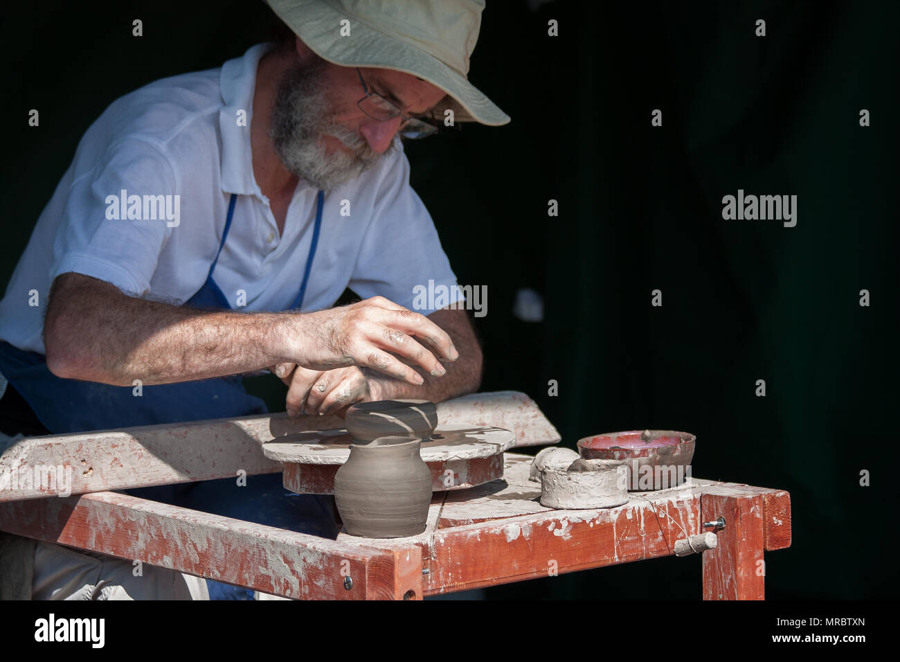 Artisan making clay pots with a manual wheel in Fountains Abbey, Ripon, UK - Stock Image
