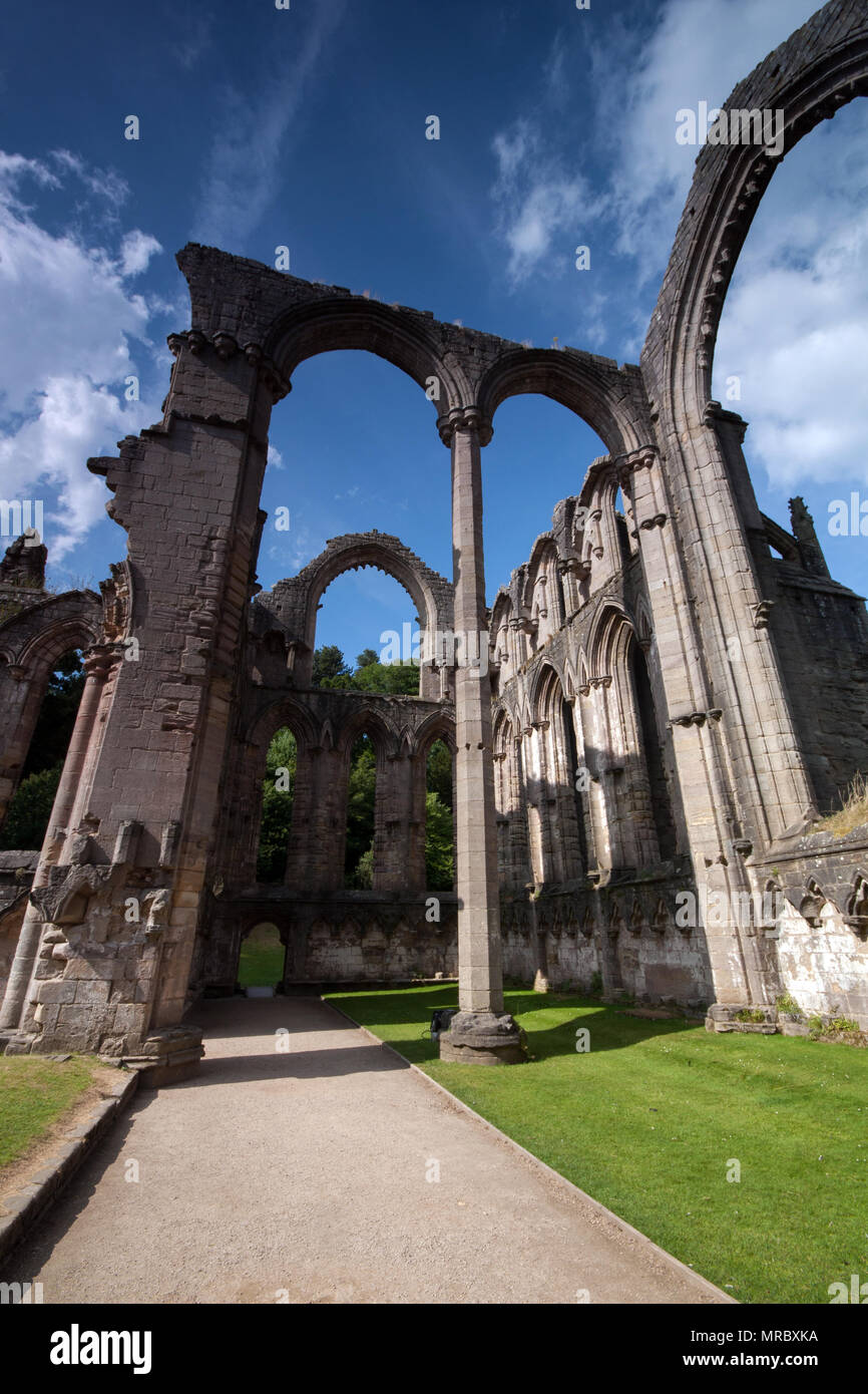 Architecture with tall gothic archs in the interior of the monastery ruins in Fountains Abbey, Ripon, UK - Stock Image