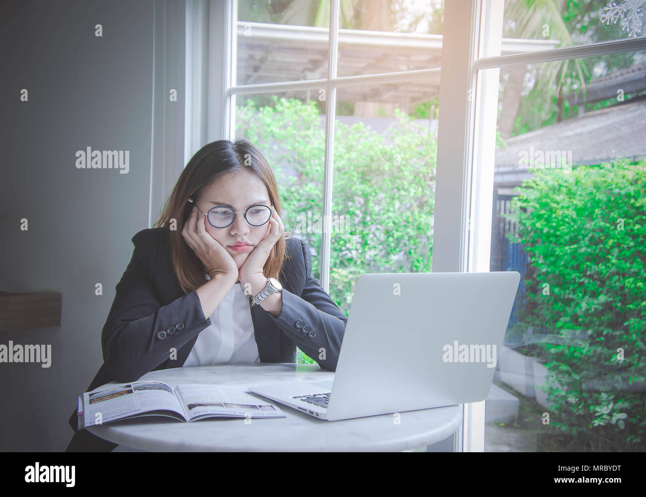 working woman , young business woman asian style busy and Stressful job There are problems in the work not thought out, resulting in unsuccessful work - Stock Image