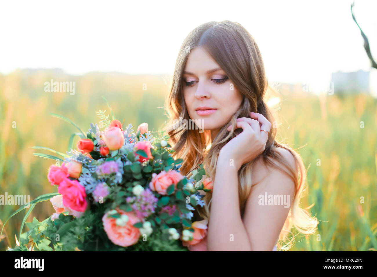 Young female person with bouquet of flowers standing in steppe background. Stock Photo