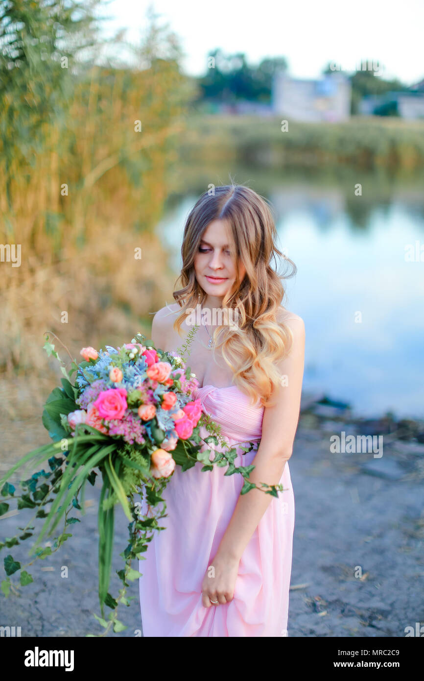 Pregnant female person wearing pink dress with bouquet of flowers standing near lake. - Stock Image