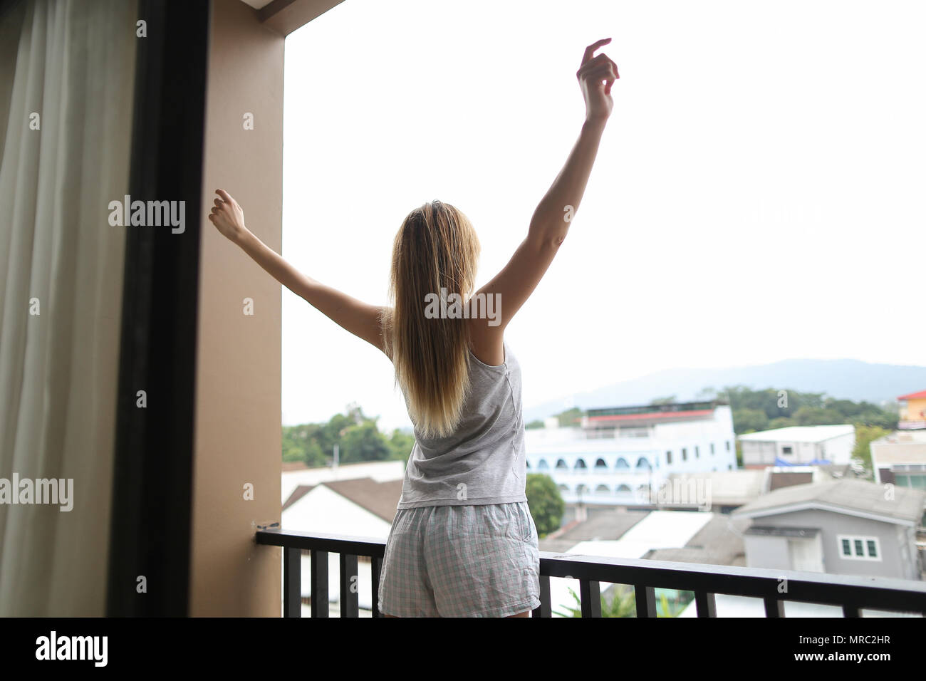 Young blonde woman wearing summer pajamas standing on balcony and looking at buildings with raised hands. - Stock Image