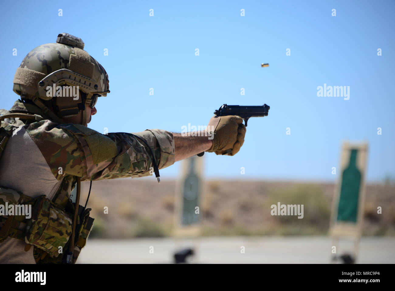 A U.S. Air Force pararescueman fires an M9 pistol at a target during the Guardian Angel Mission Qualification Training course at Davis-Monthan Air Force Base, Ariz., May 17, 2017. The MQT is a 90 day course that takes pararescuemen who have completed Air Education and Training Command schooling and helps them achieve their 5-level qualification. (U.S. Air Force photo by Airman 1st Class Nathan H. Barbour) - Stock Image