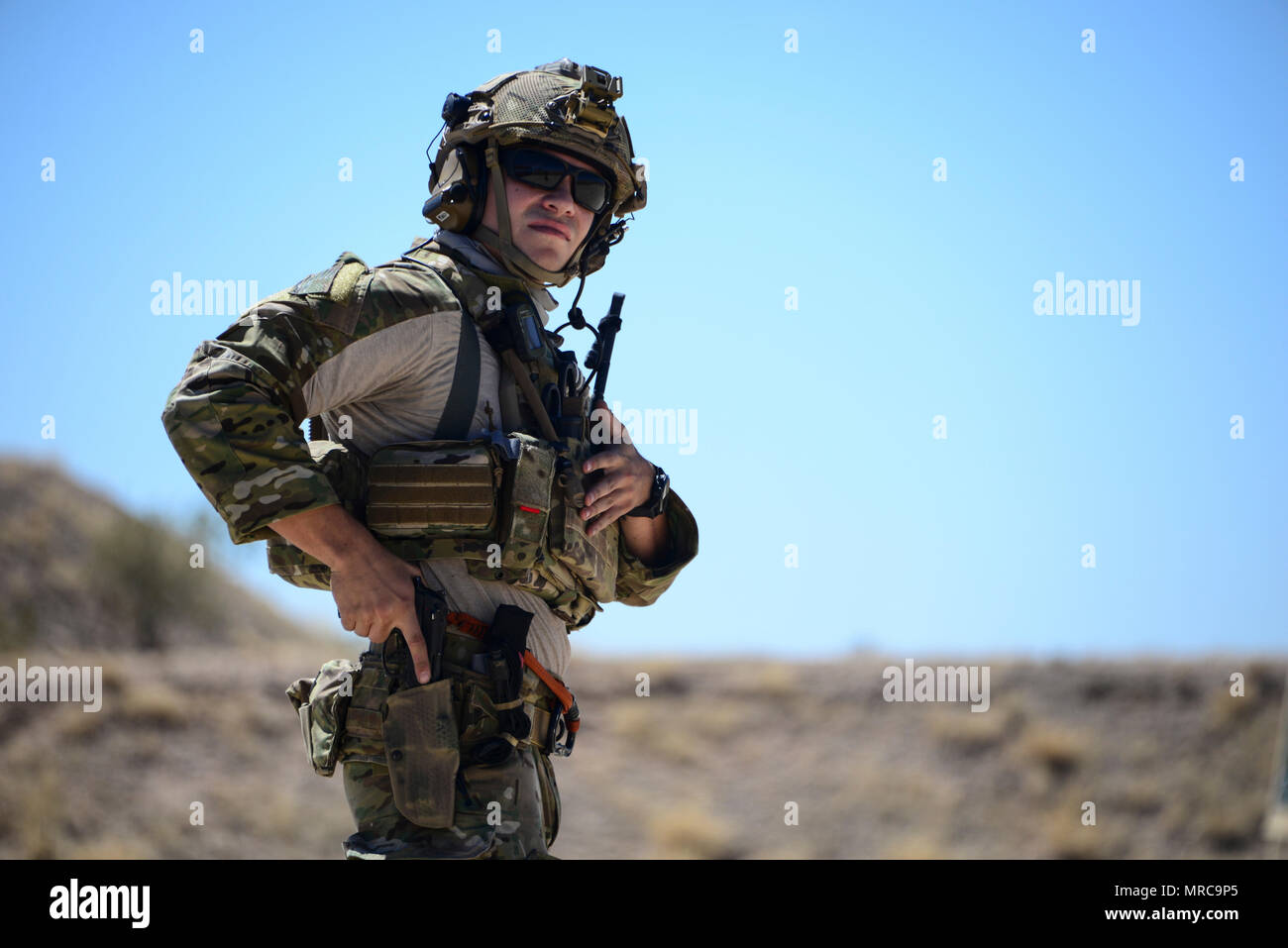 A U.S. Air Force pararescueman holsters his weapon during the Guardian Angel Mission Qualification Training course at Davis-Monthan Air Force Base, Ariz., May 17, 2017. The MQT is a 90 day GA Formal traning course that takes pararescuemen who have completed Air Education and Training Command schooling and helps them achieve their 5-level qualification. (U.S. Air Force photo by Airman 1st Class Nathan H. Barbour) - Stock Image