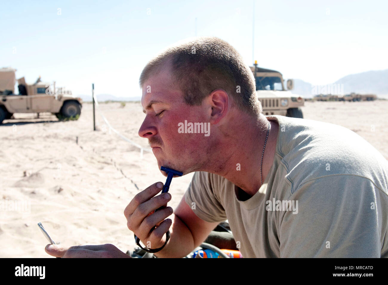 Spc. John Gore with 2d Battalion, 114th Field Artillery Regiment, shaves in the Mojave Desert using bottled water, pocket sized mirror, and a razor to conform to Army regulations at the National Training Center June 5, 2017. (Mississippi National Guard photo by Sgt. Edward Lee, 102d Public Affairs Detachment) - Stock Image