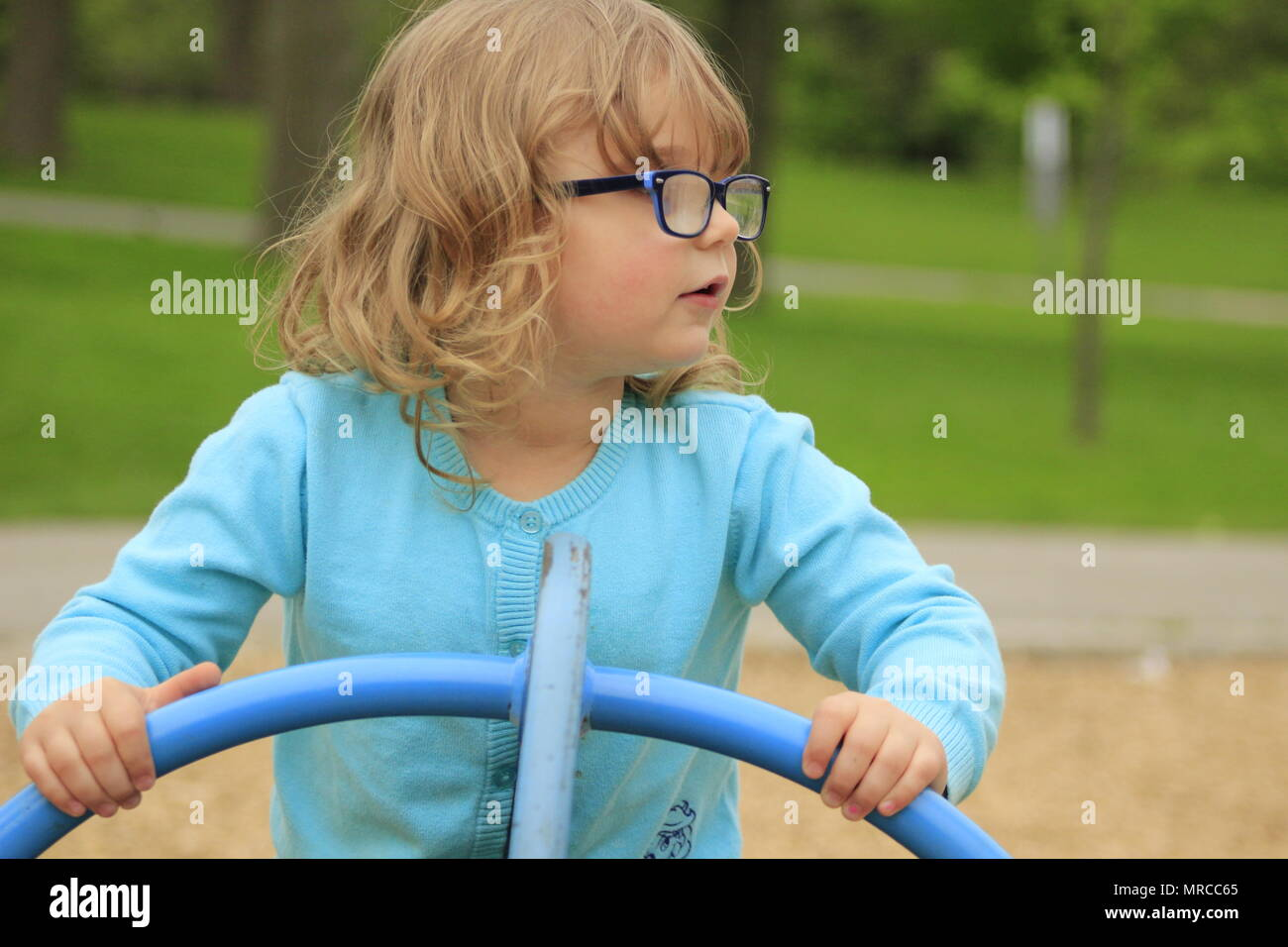 54def9a4e0da Little girl with glasses and a blue shirt playing on a playground at school  aged 3