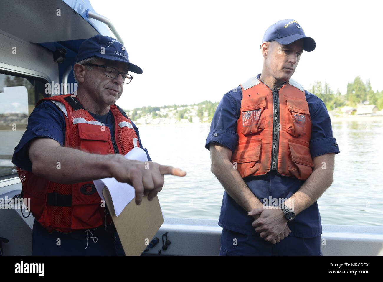 Capt. Sean Cross (right), chief of response, Coast Guard 13th District, listens as Kent Brown, a coxwain with Coast Guard Auxiliary District 13, Flotilla 1-2, conducts a safety brief prior to departing from the Naval Fuel Deport in Manchester, Wash., June 6, 2017.    Officials from the Coast Guard and Army Corp of Engineers observed a joint spill exercise off a Blake Island from Brown's vessel.     U.S. Coast Guard photo by Petty Officer 3rd Class Amanda Norcross. - Stock Image