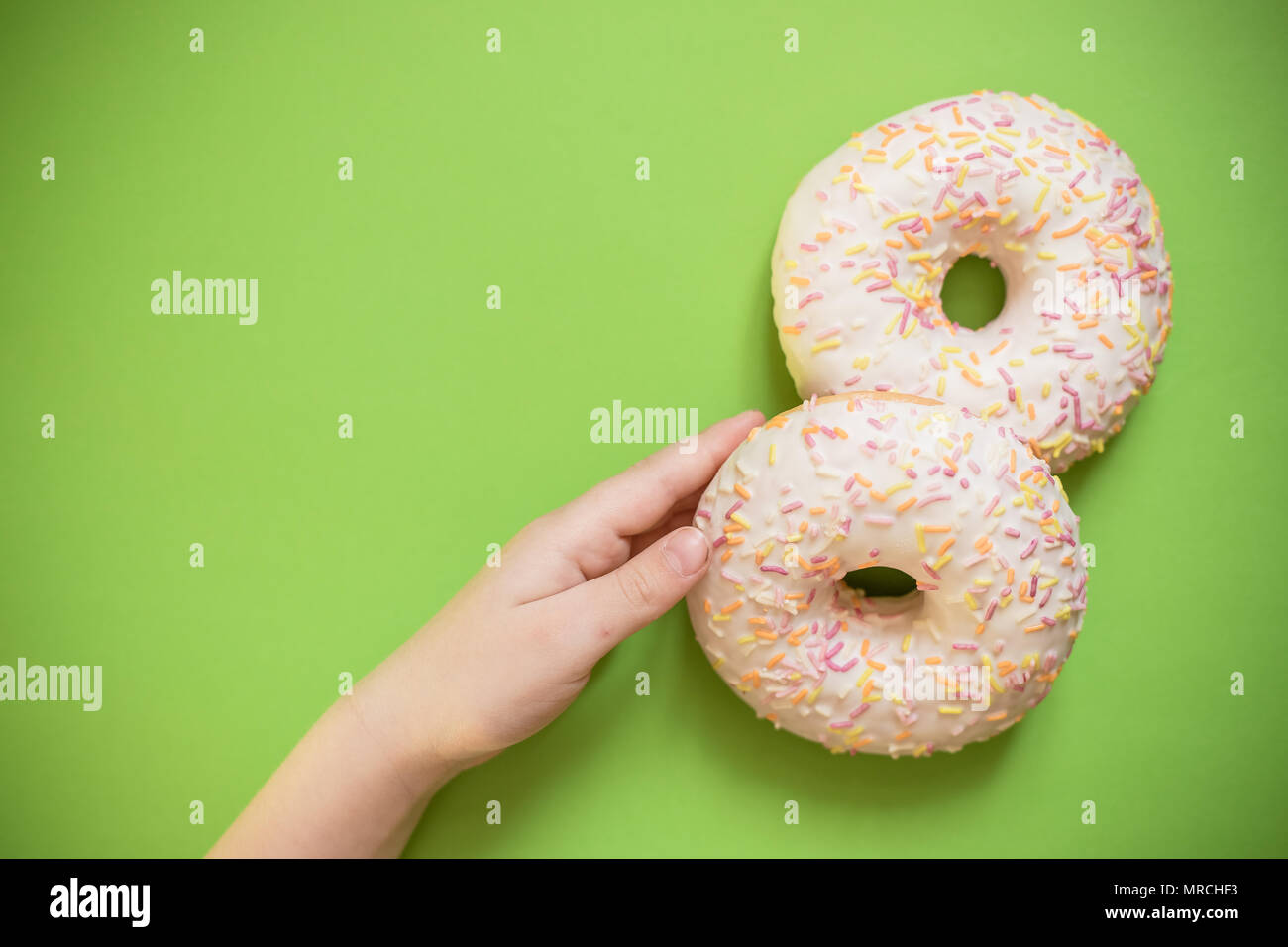 Child hand stealing the last donut from the box. Tasty sweet donuts on green background. Unhealthy sugar dessert. - Stock Image