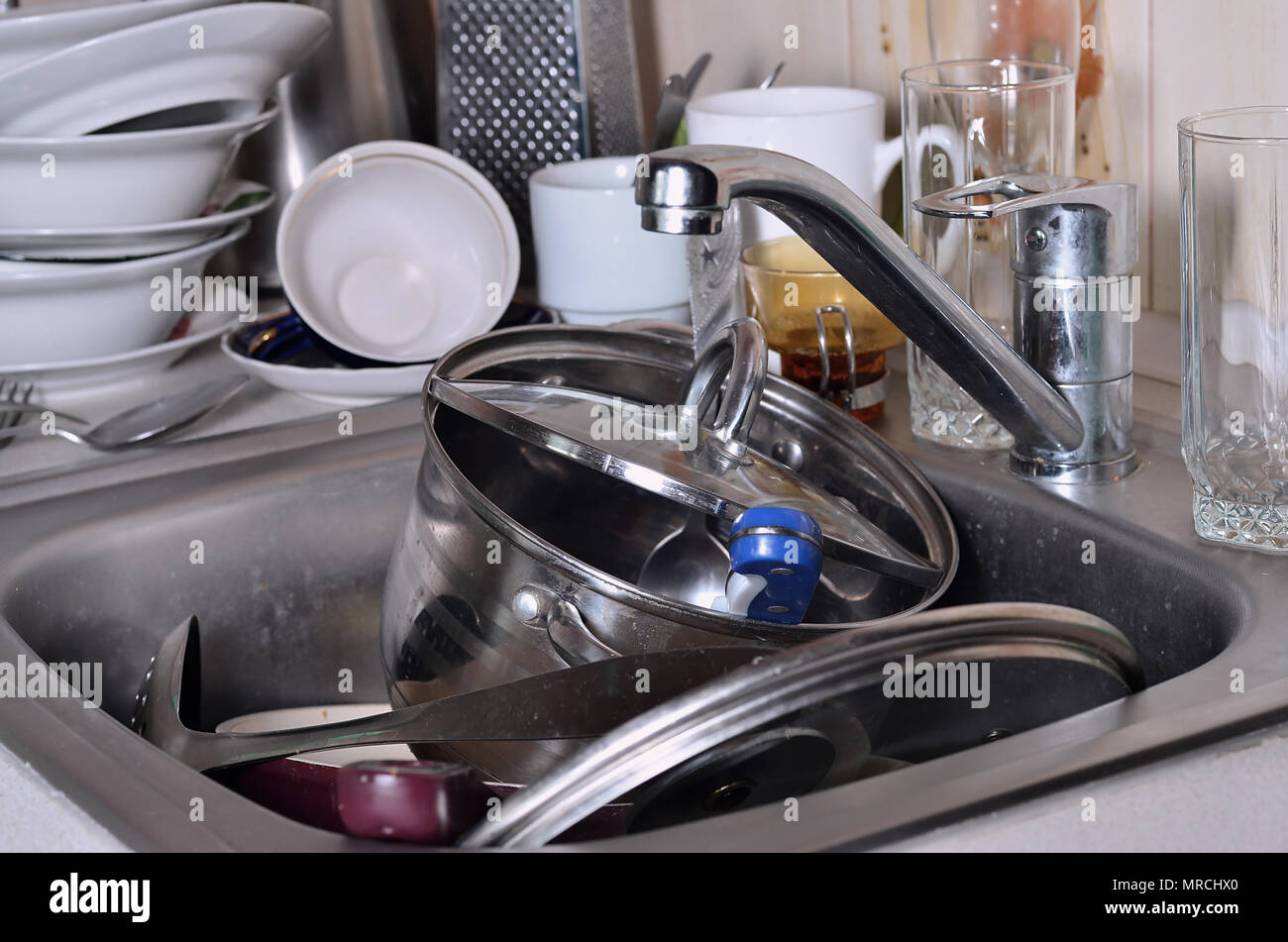 A huge pile of unwashed dishes in the kitchen sink and on the ...