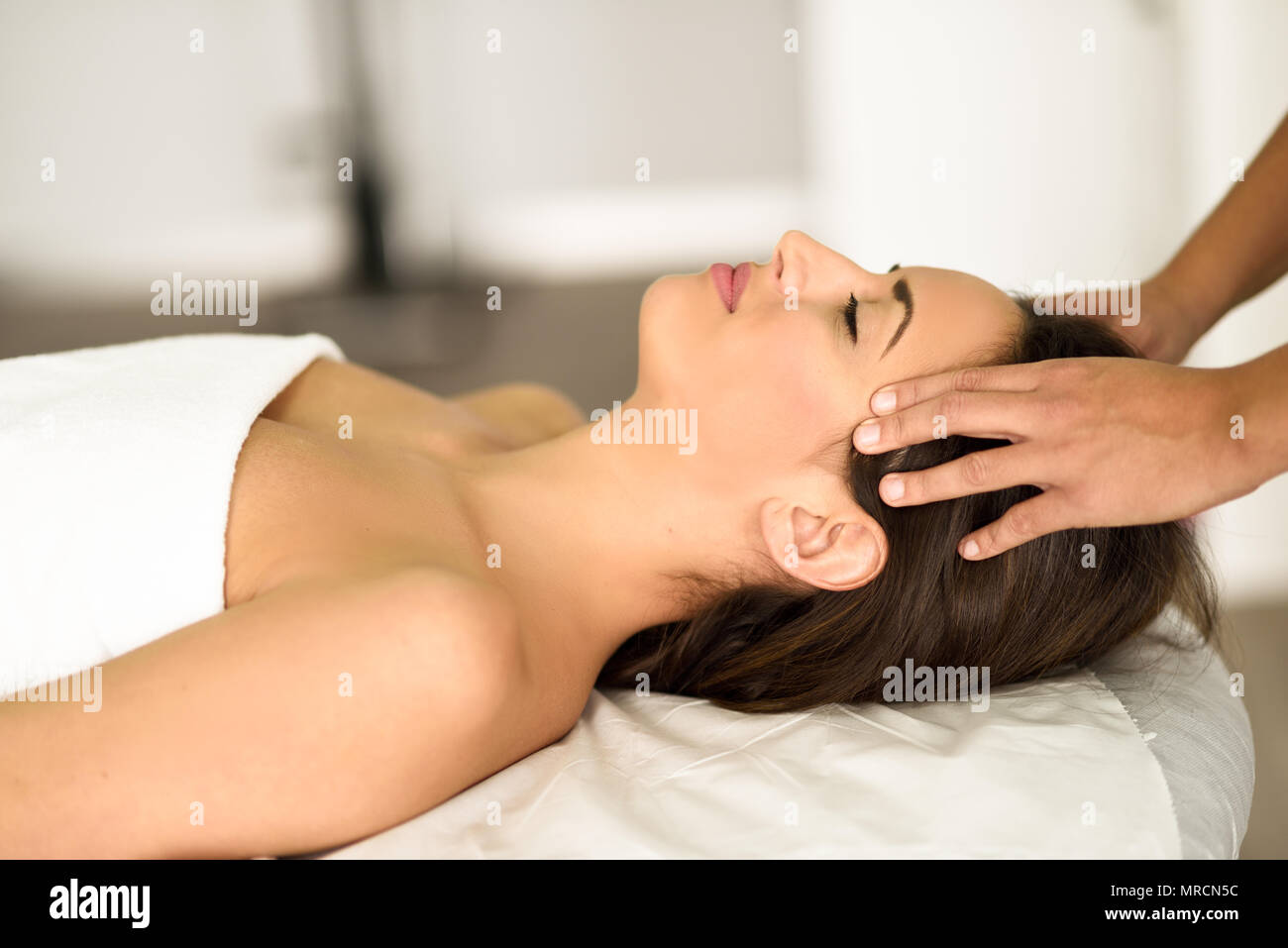 Young caucasian smiling woman receiving a head massage in a spa center with eyes closed. Female patient is receiving treatment by professional therapi - Stock Image