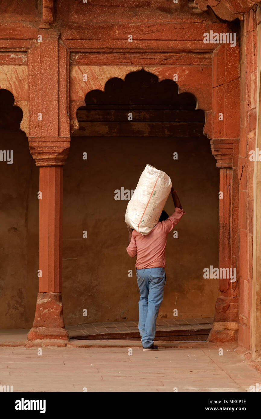 Agra, India - November 29, 2015: An Indian man carrying 'n bag on his shoulder in the historical Red Fort of Agra - a UNESCO world heritage site Stock Photo
